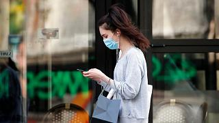 A woman wearing protective face mask looks at her phone past a closed restaurant during a nationwide coronavirus lockdown in Paris, April 20, 2020