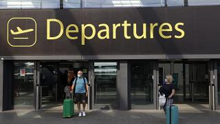 Passengers walk out of Departures, at the North Terminal of Gatwick Airport near Crawley, just south of London, Wednesday, July 22, 2020.