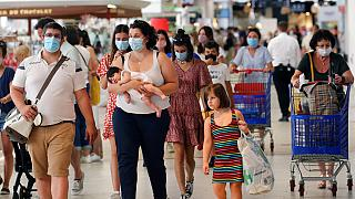 Customers wear face masks as they shop in a shopping mall in Anglet, southwestern France.