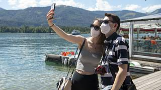 A couple make selfies at the lake side in St. Wolfgang, Austria