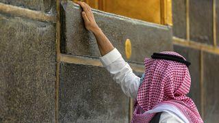 أحد المصلين يلمس جدار الكعبة