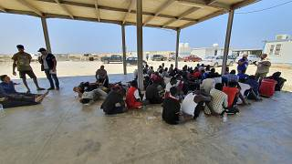 In this file photo from 2019, rescued migrants rest near the city of Khoms, around 120 kilometres east of Tripoli.