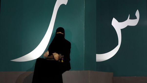 مرأة تجلس عند لافتة مكتوبة بحروف عربية خلال حدث ثقافي  حديقة الواجهة المائية بجدة/ المملكة العربية السعودية