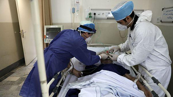 Medics tend to a COVID-19 patient at the Shohadaye Tajrish Hospital in Tehran, Iran