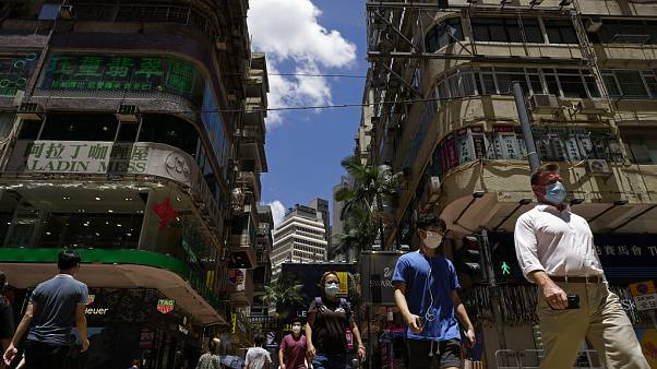 People wearing face masks to help curb the spread of the coronavirus walk on a downtown street in Hong Kong