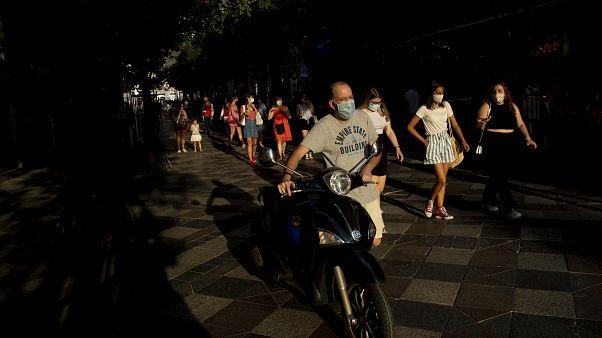 Personas con mascarillas para prevenir la propagación del coronavirus, caminan por una calle de Madrid, España, el  28 de julio de 2020.
