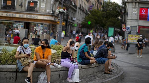 People wearing face masks to prevent the spread of coronavirus, sit on a bench street in downtown Madrid, Spain, Tuesday, July 28, 2020.
