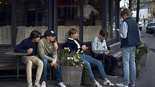 Youth hang out outside a restaurant in Stockholm, Sweden, Wednesday, April 8, 2020