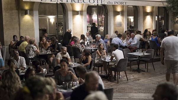 A couple sits for dinner at a crowded restaurant in Marseille's Old Port, southern France, Saturday, July 25, 2020.