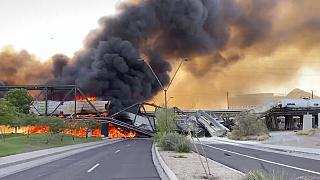 Smoke fills the sky at the scene of a train derailment in Tempe, Arizona