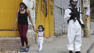 Una mujer y una niña pasan junto a un militar con traje de protección en Bogotá, Colombia