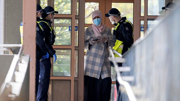 Police talk to a woman at housing commission apartments under lockdown in Melbourne, Australia, on Monday, July 6, 2020.