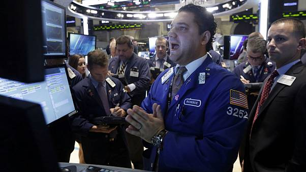 Specialist Ronnie Howard, center, calls out prices as he works at his post on the floor of the New York Stock Exchange