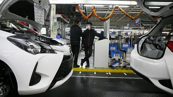 Employee wearing a face masks stand by the production chain of the Yaris car at the Toyota car factory in Onnaing, northern France