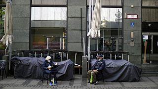 An elderly couple sit outside a closed bar in Munich, Germany