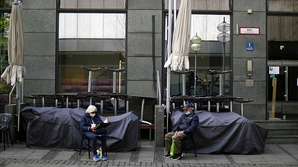 An elderly couple sit outside a closed bar in Munich, Germany