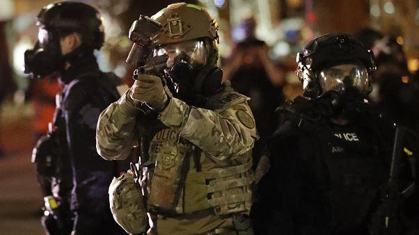 شرطي فدرالي يوجهه سلاحه إلى المتظاهرين