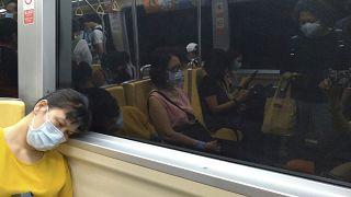 سيدة تجلس في مترو لندن مرتدية الكمامة