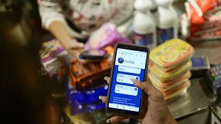 Una empleada muestra su teléfono móvil mientras calcula el monto de la compra en Petros en una tienda  donde se acepta la criptomoneda venezolana, en Caracas, Venezuela.