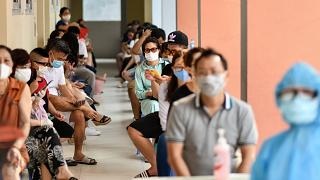 Residents wait to be tested at a centre as Vietnam records a rise in COVID-19 cases
