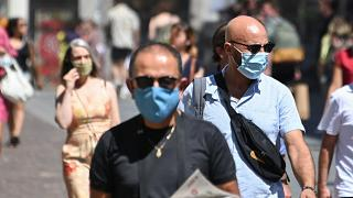 People wearing protective masks walk on a street in Lille, France