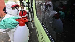 Un empleado con equipamiento de protección limpia un vehículo de transporte público en Ciudad de México