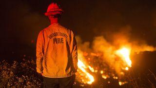 Un bombero observa un incendio de matorrales en el incendio de Apple en Banning, California, el sábado 1 de agosto de 2020.