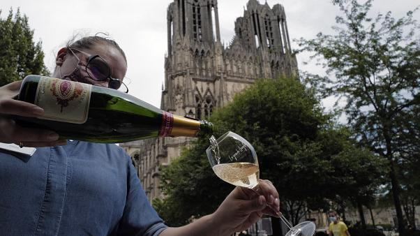 A waitress serves a glass of champagne at La Grande Georgette restaurant in front of the cathedral in Reims, onTJuly 28, 2020.
