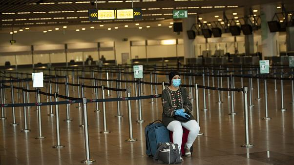 sits at the almost empty departures hall at the Zaventem international airport in Brussels, Wednesday, July 29, 2020.