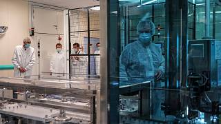 In this June 16, 2020, file photo, French President Emmanuel Macron listens to a researcher as he visits an industrial development laboratory  at Sanofi Pasteur plant ,