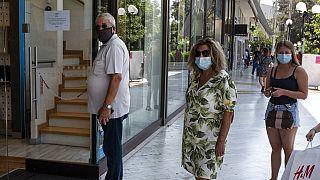 Πολίτες φορούν μάσκα και περιμένουν στην ουρά