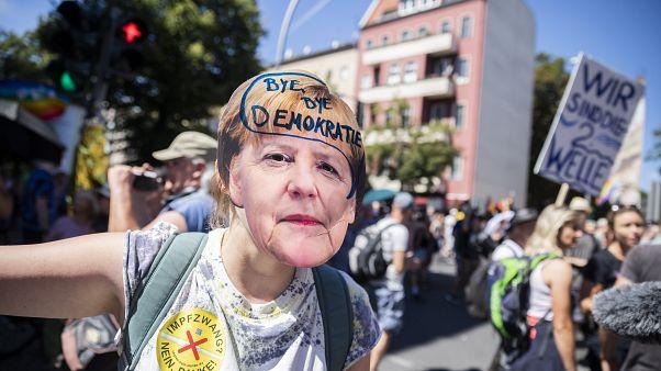 """Una mujer lleva una máscara de Angela Merkel con la inscripción """"adíos democracia"""" en la manifestación contra las restricciones en Berlín, Alemania, el 1 de agosto, 2020."""