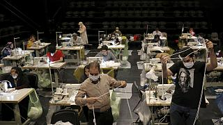 Volunteers wearing face masks to curb the spread of the new coronavirus, sew face masks for poor people, at the Hafez theatre hall in downtown Tehran, Iran