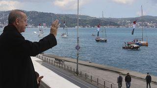 O T. Ερντογάν χαιρετά πλοία διακοσμημένα με την τουρκική σημαία κατά τους εορτασμούς για την κατάκτηση της Κωνσταντινούπολης