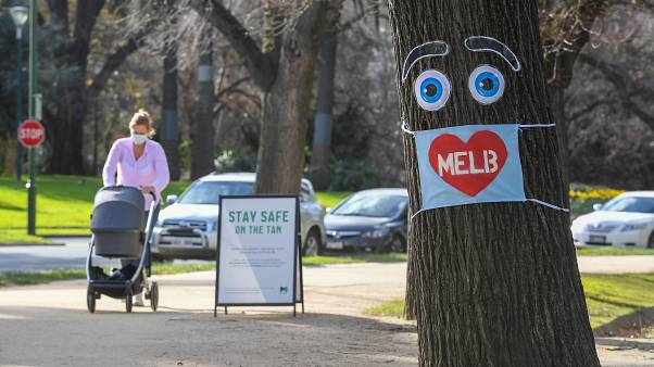 A woman pushes a pram past a large face mask pinned to a tree in Melbourne on August 3, 2020 after the state announced new restrictions as the city battles fresh outbreaks.