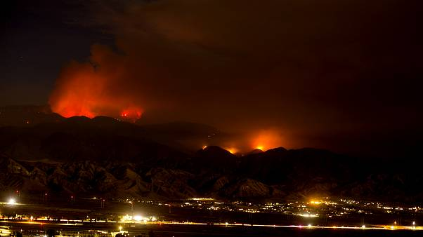 The Apple Fire burns behind mountains near Beaumont, California, Sunday, August 2, 2020.
