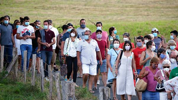 People wear face masks as they leave a music festival in Saint Etienne de Baigorry, southwestern France, Sunday, July 26, 2020.