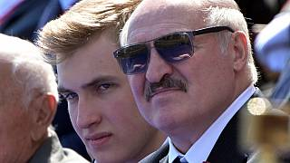 This handout picture provided by Host photo agency shows Belarus's President Alexander Lukashenko and his son Nikolai watching a military parade