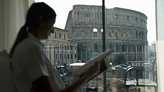 Una turista in una camera di hotel a Roma, con il Colosseo sullo sfondo
