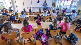 Teacher Francie Keller welcomes the pupils of class 3c in the Lankow primary school to the first school day in Schwerin, Germany, Monday, Aug. 3, 2020.