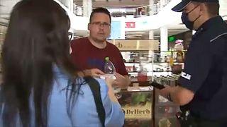 Rendőr ellenőrzi a maszkviselést egy lengyelországi bevásárlóközpontban