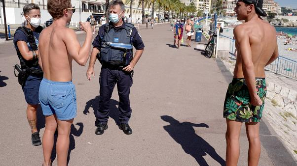 """Des policiers informent les gens du port obligatoire du masque sur la """"Promenade des Anglais"""", à Nice, le 3 août 2020"""