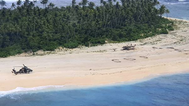 In this photo provided by the Australian Defence Force, three men stand the beach on Pikelot Island in the Federated States of Micronesia