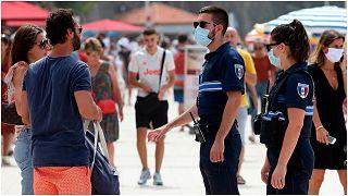أفردا من الشرطة الفرنسية ينصحون مواطنين بارتداء الكمامات في بياريتز، جنوب غرب فرنسا