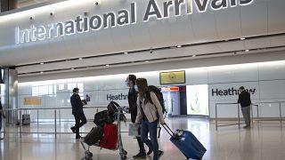 Pasajeros con mascarillas llegan al aeropuerto londinense de Heathrow, 8/10/2021
