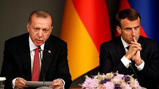 Turkey's President Recep Tayyip Erdogan, left, sits by French President Emmanuel Macron during a news conference following a summit on Syria, in Istanbul, Saturday, Oct. 27, 2
