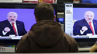 Belarus's President Alexander Lukashenko is seen on TV screens inside a shop