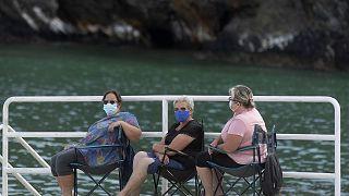 ثلاث نساء ترتدين كمامات في بورتو أو باركيرو في شمال غرب إسبانيا