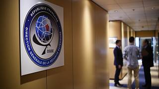 Three men speak in a corridor at the headquarters of the General Directorate for External Security (DGSE)