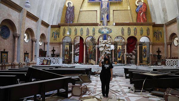 Nő készít képeket egy megsérült keresztény templomban szerdán